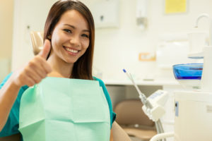 woman thumbs up dental chair