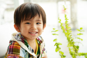little boy smiling beside plant