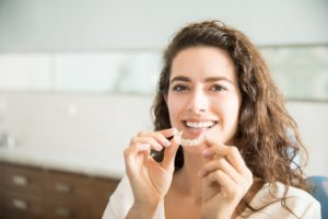 Woman holding clear aligners in Southlake.